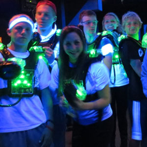 Laser tag group of 6 teenagers in matching white shirts